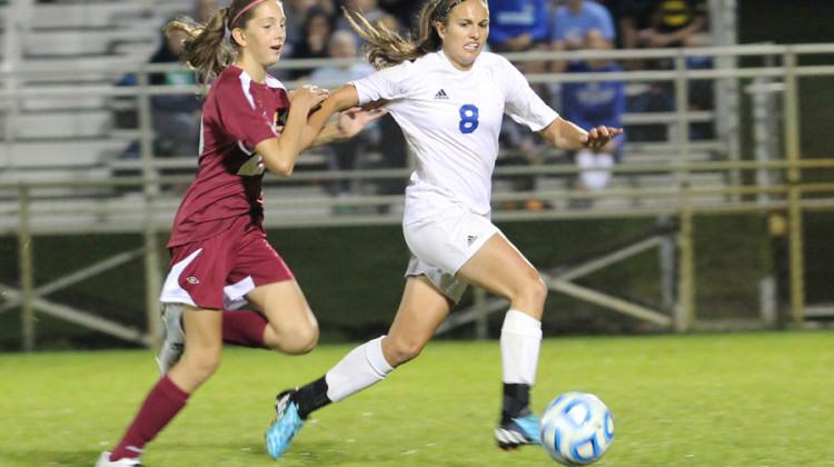 Brianna Dougherty (12) fights off a Chesterton defender. Dougherty scored both goals of the night for the Lady Indians.