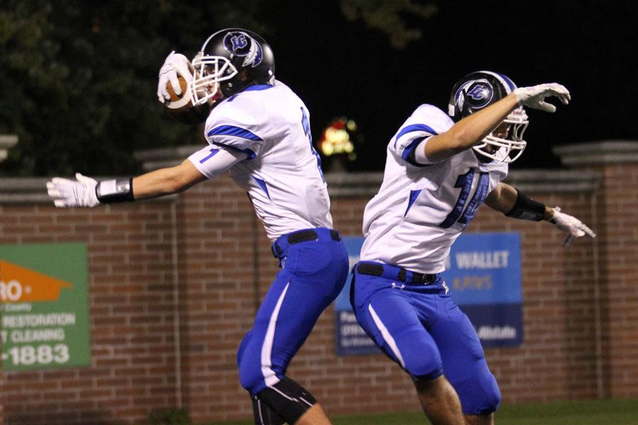 Austin Atkins (10) celebrates with Cody Schultz (12). After Atkins caught his second touchdown pass of the night, Schultz decided to perform a shoulder bump with him.