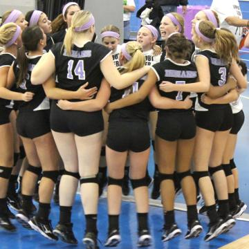 The girls varsity volleyball team huddles before the game. The girls went into the game with high spirits.