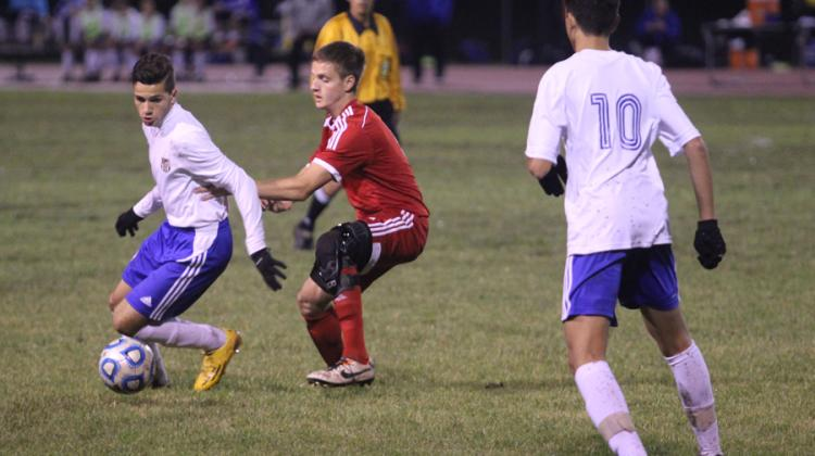Naser Tahawah (10) attempts to keep the ball away from a Munster player with the help of Michael Flores (12). The game's final score was 1-0.