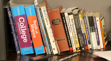 A row of books sit stacked on a shelf in the guidance office. The books, with topics ranging from majors to scholarships, can be used by students.