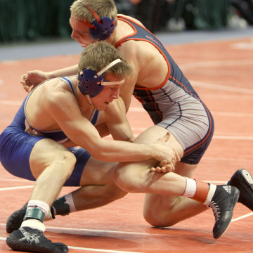 Kodie Christenson (12) holds on to his opponent's leg. Christenson qualified for the State Finals by placing third at Semi-State.