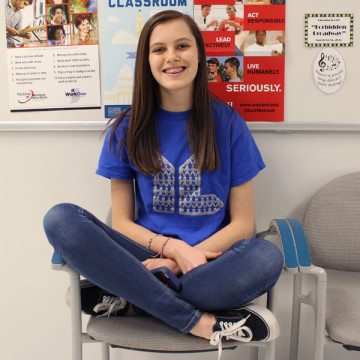 Hailey Phelps (10) wears her Young Life t-shirt while sitting on a chair in the hallway.  She got the t-shirt from the group, which usually met on Wednesdays.
