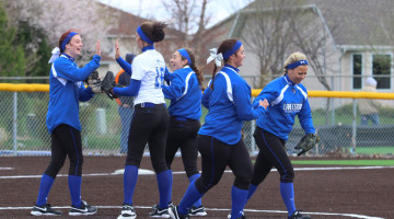 The girls on the field high-five each other on the mound after a good pitch by Annabel Karberg (12). During game, after each accomplishment, the ladies encouraged each other.