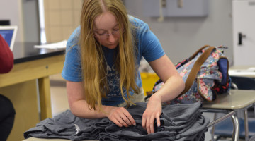 Ashley Millette (12) counts the number of shirts that were sold. The club sold the shirts to honor Earth Day.