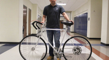 Mr. Eric Graves, Math, poses in the hallway with his bike that he rides to and from school. The bike, which was in poor condition when Graves originally discovered it, has been restored by him and is now used as a means of transportation, exercise and a way to save money.