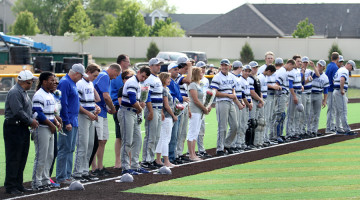 The varsity baseball team stands on the third base line before the game on Friday, May 23 against Hobart. The team beat the Brickies in a 10-1 victory.