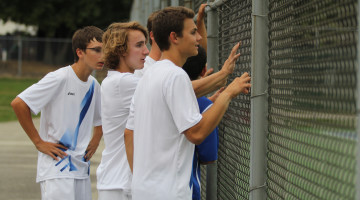 The boy's tennis team watches the last match finish. The boys won 5-0.