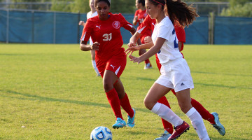 Cevanah Brazzale (9) battles for the ball with two girls from Portage. She took the ball and dribbled it down the field.