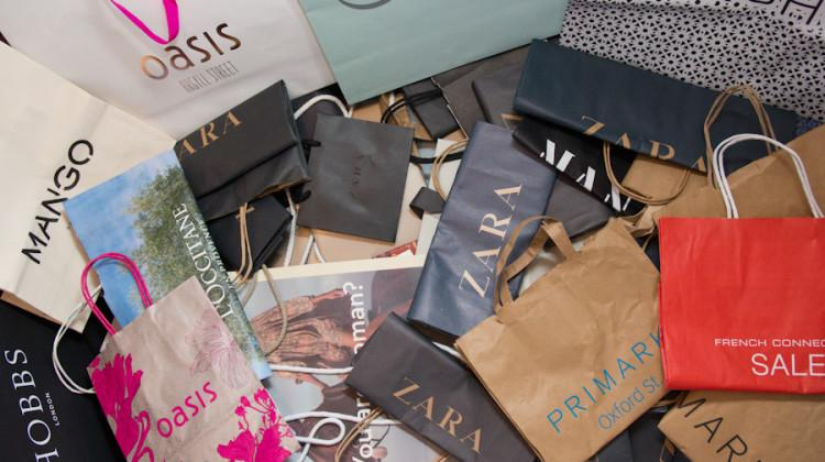 Various shopping bags lay stacked in a large pile. Many stores announced their plans to open earlier this year.