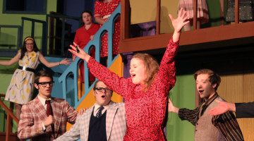 Elise Bereolos (12) sings in front of Brett Balicki (12), Jackson DeLisle (12) and Zachary Hansen (11). Bereolos played the character Miss Jones, a secretary to the boss of the company in the production.