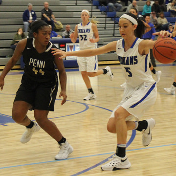 Victoria Gard (12) tries to block her opponent while dribbling the ball. Gard passed the ball to one of her teammates.