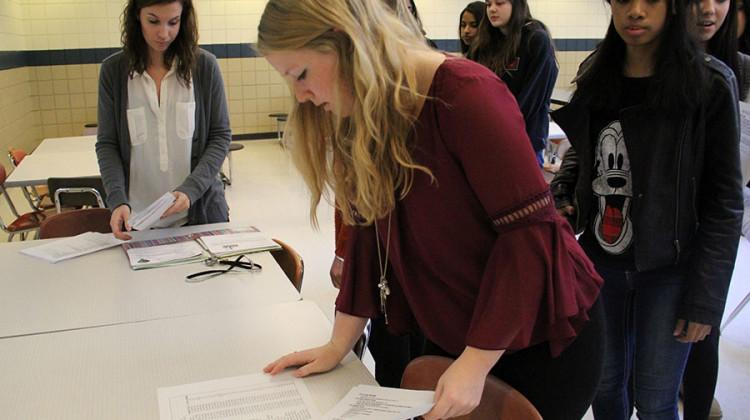Members of N-Teens line up to check their name on a list. The paper listed all students signed up to go on the Chicago trip which will take place on Saturday, Dec. 5.