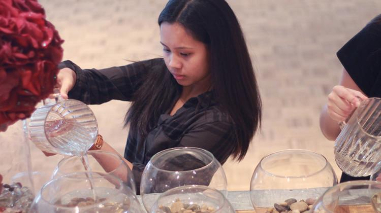 Melicah Rodriguez (10) fills the centerpiece with water. The decorations featured a bowl with floating flowers.