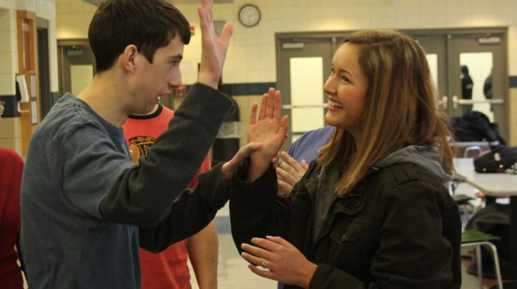 Jack Rogers (11) goes to high-five Madeline Young (12) after playing a game of 'Simon Says.' Rogers and Young were partners for all of the activities during the meeting.