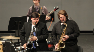 Two tenor saxophone players, Nicholas Perez (12) and Benjamin Moore (12), stand for their solos. Perez and Moore were part of the Jazz II band.
