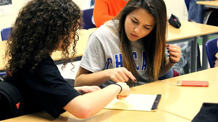 Mariah Meyer (9) and Mya Poulos (10) fill out the sign in sheet at the beginning of the meeting. For students to be a part of the team they must have a white card.