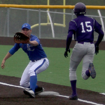 Jake Wisniewski (12) attempts to catch the ball to get the Merrillville runner out at first. The Indians only gave up one hit throughout the game.