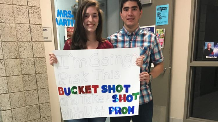 "Mohammed Hijaz (11) and Samantha McCuaig (11) stand behind the sign Hijaz made to ask McCuaig to Prom. Hijaz had shot ping pong balls labeled, ""Prom?"" to her using air trajectory. 