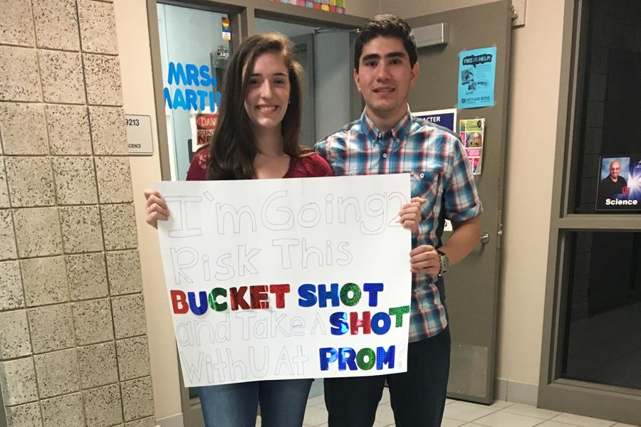 "Mohammed Hijaz (11) and Samantha McCuaig (11) stand behind the sign Hijaz made to ask McCuaig to Prom. Hijaz had shot ping pong balls labeled, ""Prom?"" to her using air trajectory.  Photo submitted by Mohammed Hijaz (11)"