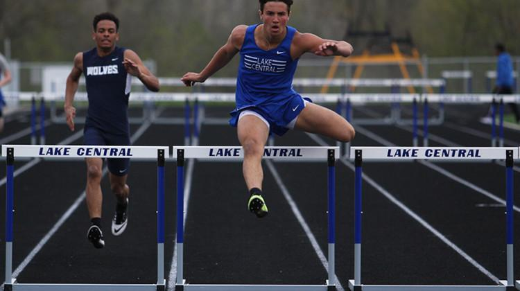 Nick Lucas (11) jumps over a hurdle during the 300-meter hurdles event.  Lucas received second place with a time of 44.87 seconds.