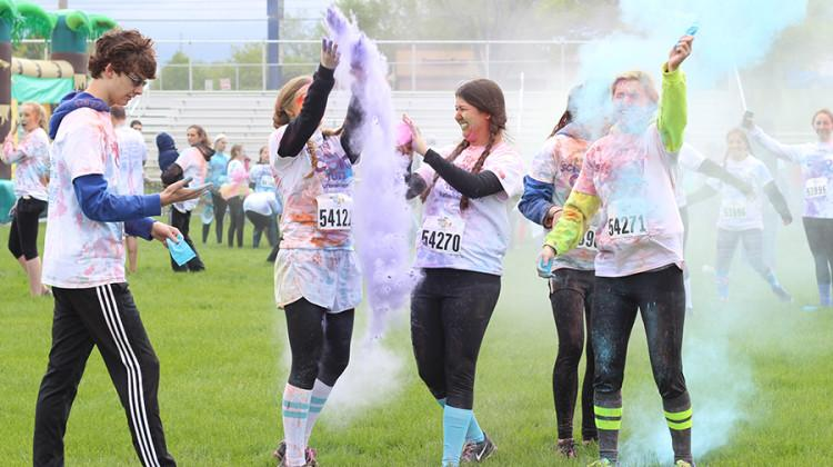 Samuel Michniewicz (11), Autumn Napiwocki (11), Alexa Szatkowski (11), Michelle Buckman (11) and Madelyn Long (11) throw their color packets into the air after the Color Run. Most participants threw packets around at each other after the race for personal enjoyment.