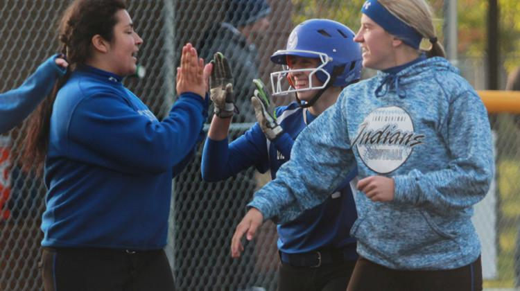 Crystal Guzman (11) high-fives her teammates, Cheyenne Mathas (10) and Julia Schassburger (12). Guzman's triple ended the game.