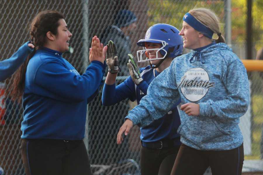 Crystal Guzman (11) high-fives her teammates, Cheyenne Mathas (10) and Julia Schassburger (12). Guzman's triple ended the game.