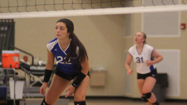 Waiting for the ball to be returned over the net, Alyssa Gomez (10) plays defense. Gomez was also chosen to dress for the varsity match.