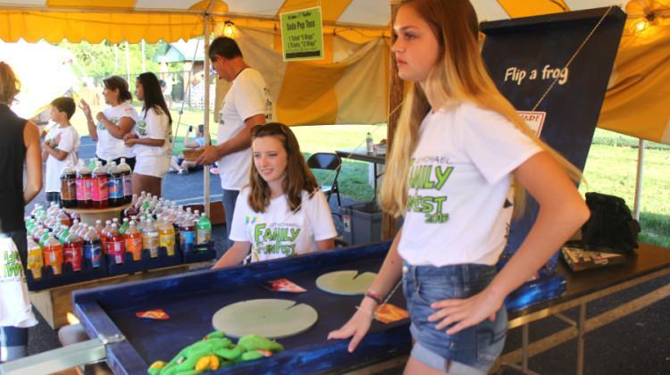 McKenna Strayer (11) and Erin Pleuntes (11) help the frog game. Strayer and Pleuntes stayed at the fest later in the evening.