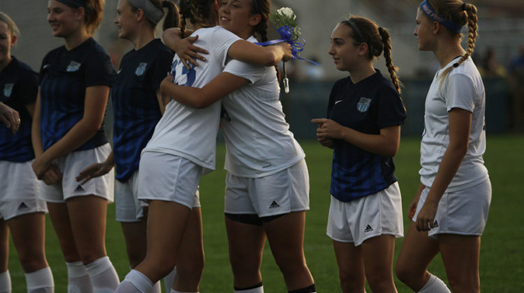 Meghan Teumer (12) hugs teammate while walking out for Senior Night. Teumer's teammates gave hugs to all the seniors when the walked out.