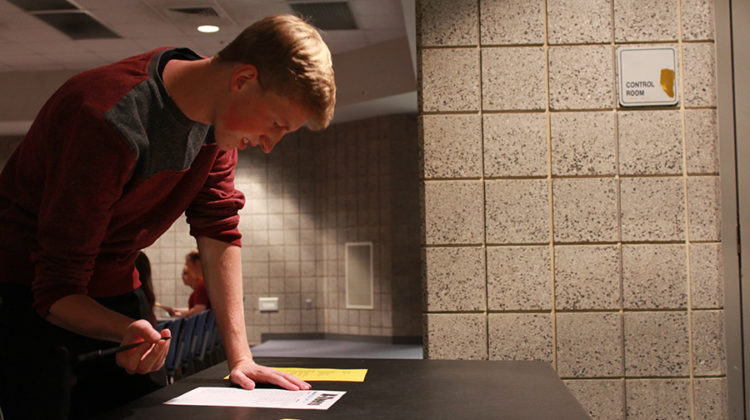 Brett Szabo (12) fills out his name and grade on the N-Teens sign-in sheet. N-Teens held their second meeting on Sept. 27.