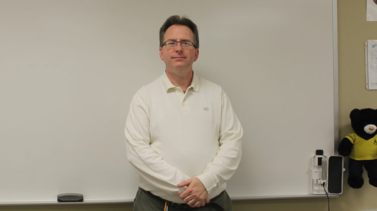 Mr. Harnish stands in his high school classroom. He has been teaching college courses at Indiana University.