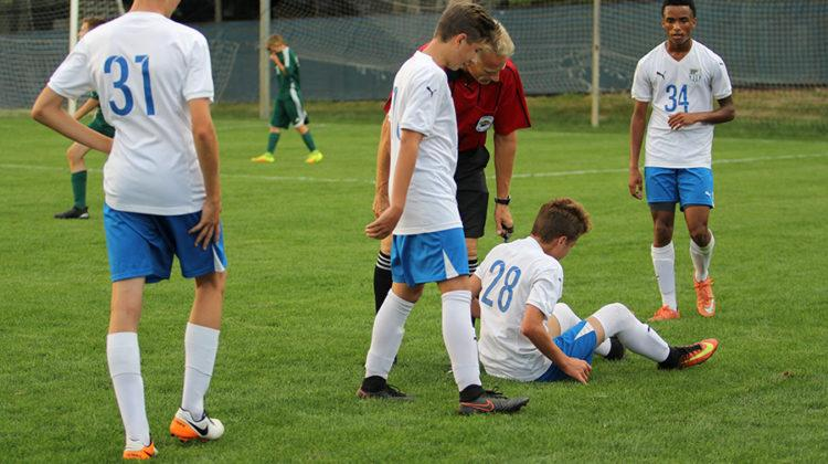 Teammates check on Robert MacNeill (9) after a hard tackle. The referee gave Lake Central a free kick after this.