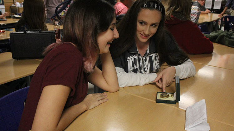Molly Fischer (10) and Mia White (10) gaze at a World War II commemorative pocket watch. The watch was one of the many items examined at History Club.