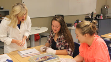 Mrs. Parks, Jessie Balka (11) and Nina Zochalski (11) all discuss the internal structure of the rat. Students in Honors Anatomy participated in the lab.