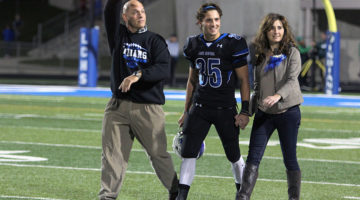 Nicholas Lucas (12) walks down the field as his dad points toward him while the fan section chants his last name. Lucas was escorted by his parents during the senior night portion of the game which took place on Oct. 14.