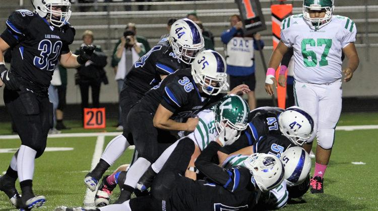 The Indians tackle the Trojans to block them from completing a play. Lake Central won the game with a score of 21-20.