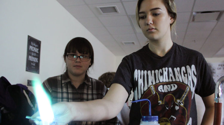 Kaylyn Lee (10) and Allison Magura (10) observe the flame to identify what chemical was being burned. Chemicals that burned blue had a high energy.