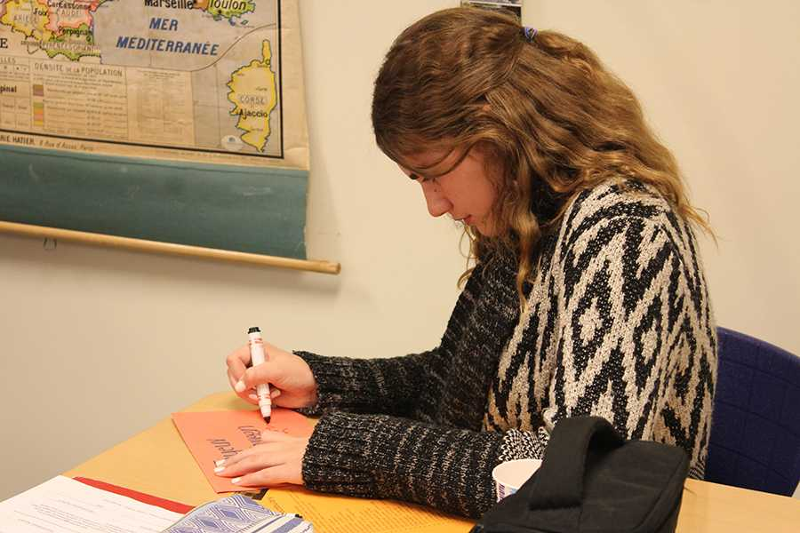 Claire Karberg (10) makes a Halloween themed card at French club on October 25. Students made Halloween themed crafts at the meeting.