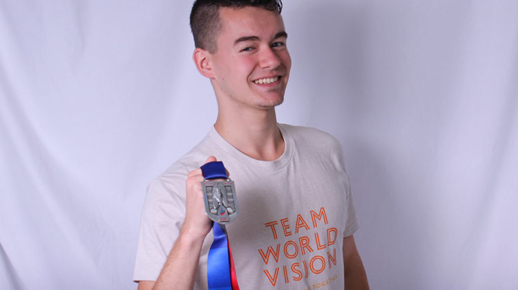 Michael Clark (12) poses with his medal he received after finishing the Chicago Marathon. This was the third time Clark participated in that marathon.