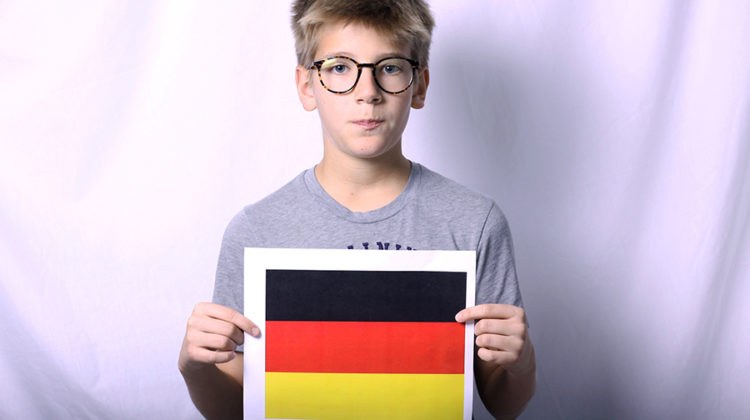 Paul Jochmann (9) poses for the photo as he holds a paper with the German flag on it.  Jochmann was not been very excited about his move to America.