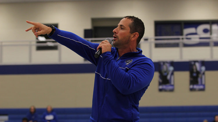 Head coach of varsity football, Tony Bartolomeo, Science, speaks in front of the students body during the Homecoming pep rally. Bartolomeo, who took over as head coach on Sept. 13, coached the team to a 38-0 victory later that day.