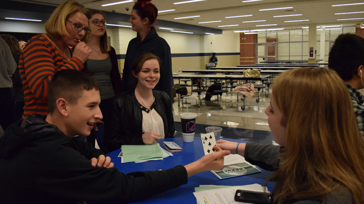 These Campus Life members are playing a card game while waiting for the leaders to announce that the meeting is starting.  The card game was a magic trick that was started by Tony Pacheco (10).