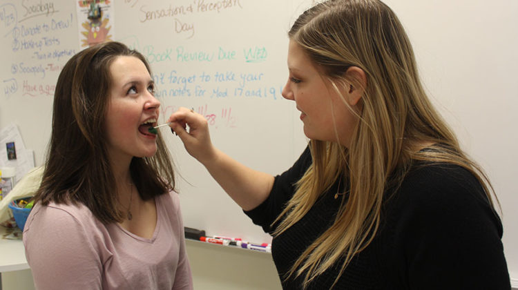 Olivia LaVoie (10) gets her tongue painted green by Madison Frederick (11) on Sensation Day in AP Psychology class. LaVoie turned out to be a supertaster.