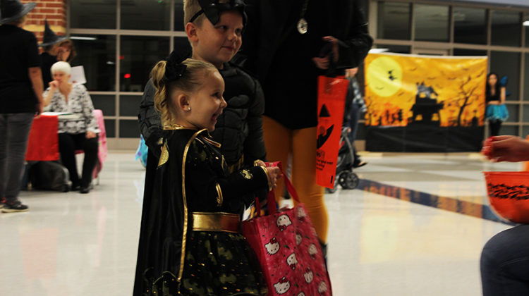 Two young children, dressed as Batman and Batgirl, smile at a student's costume. Ghouls at the School started at 5 p.m. and ended at 8 p.m.
