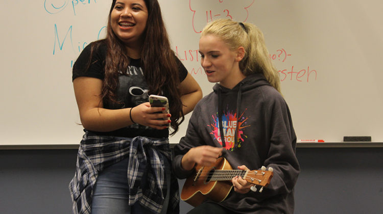 """Jocelyn Hansen (9) holds up lyrics for Ava Solis (9) who sings """"Spirits"""" by The Strumbellas. Hansen held up lyrics for multiple people throughout this Open Mic meeting."""