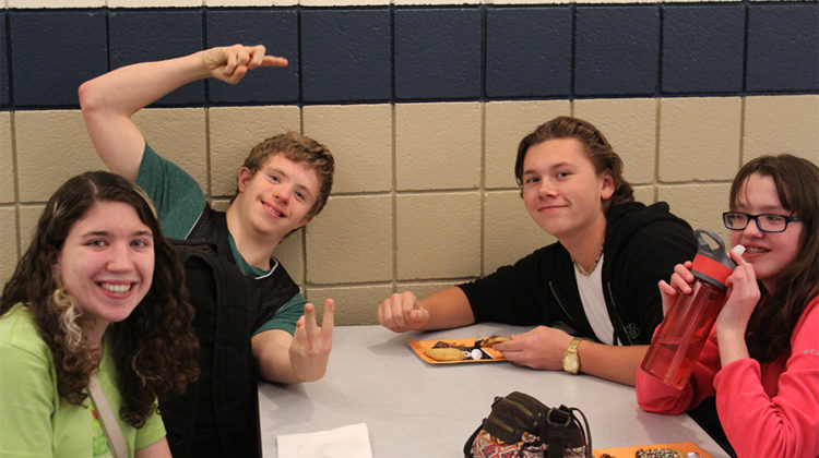 Charlie August (10) interacts with buddies at the Best Buddies meeting.  The club members decorated cookies and sang along to Christmas music.