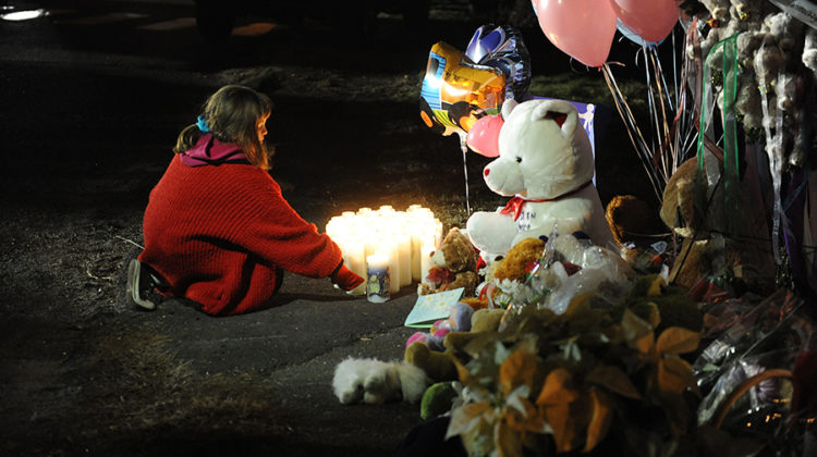 A girl lights candles at a memorial near Sandy Hook Elementary School on Saturday, December 15, 2012 in Newtown, Connecticut, a day after a shooting rampage at the school. (Olivier Douliery/Abaca Press/MCT)