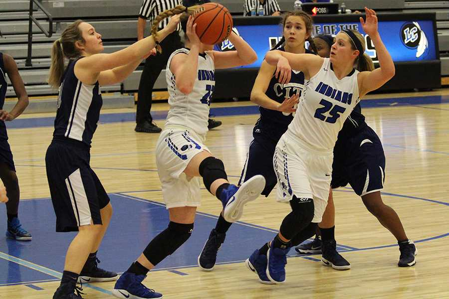 Bailey Fehrman (10) and Meghan Long (10) try to get the ball away from the opposing team. The final score was 57-17.
